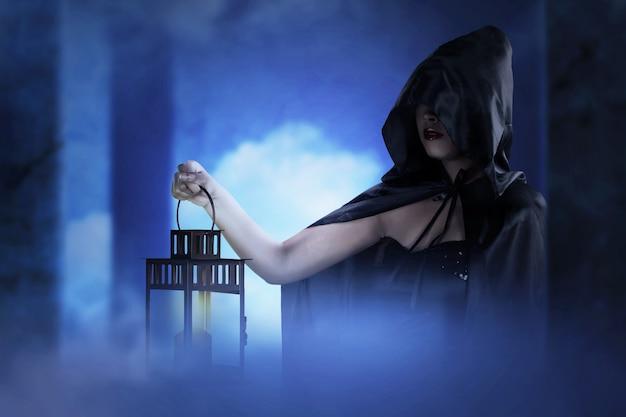 Азиатская женщина-ведьма с черным плащом держит фонарь в заброшенном здании. концепция хэллоуина