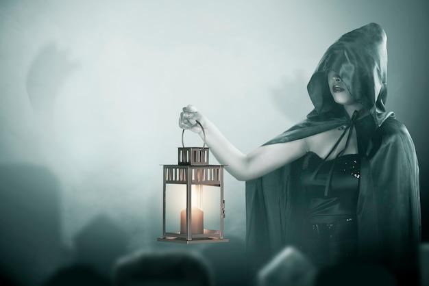 墓地に立っているランタンを保持している黒いマントを持つアジアの魔女の女性