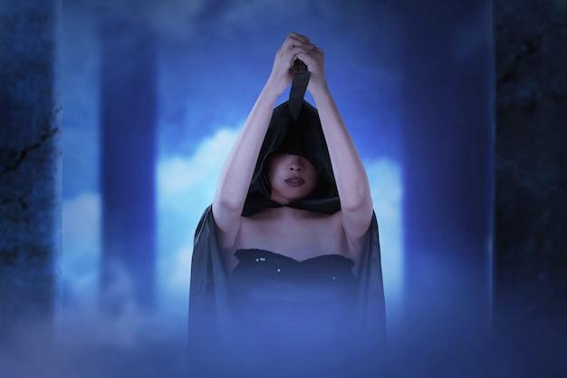 放棄された建物に立っているナイフを保持しているマントを持つアジアの魔女の女性。ハロウィーンのコンセプト