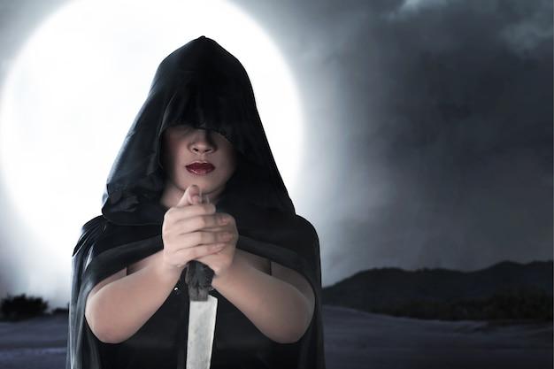 ナイフを持っているマントを持つアジアの魔女の女性