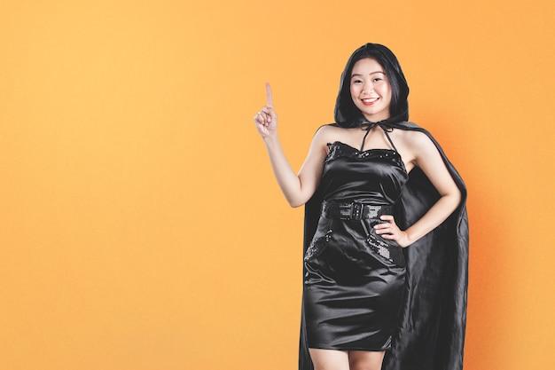 Азиатская женщина-ведьма с плащом, указывая что-то на цветном фоне