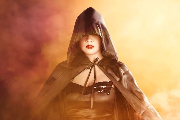 劇的な背景で立っているマントを持つアジアの魔女の女性