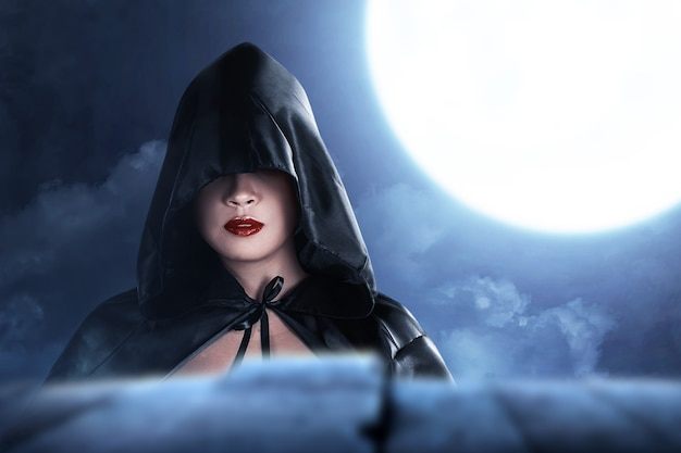 夜のシーンの背景と立っているマントを持つアジアの魔女の女性