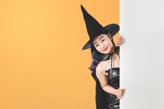 Азиатская женщина ведьмы в шляпе стоя с пустой доской с цветным фоном. пустая доска для копирования пространства