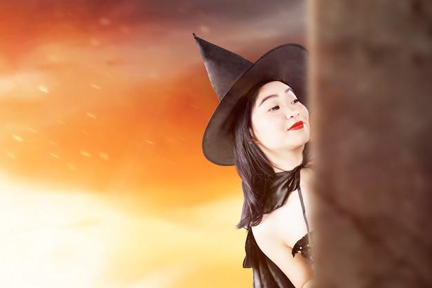 劇的な背景で立っている帽子を持つアジアの魔女の女性
