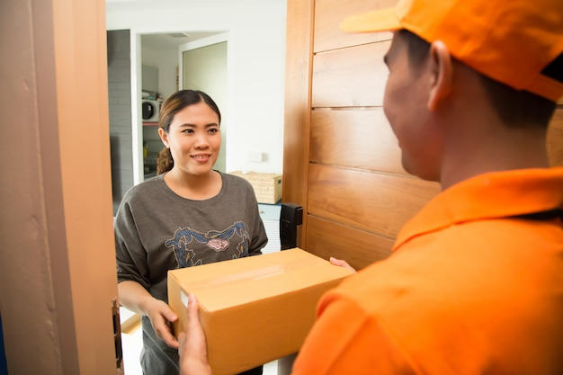 Asian woman accepting a delivery of boxes from deliveryman