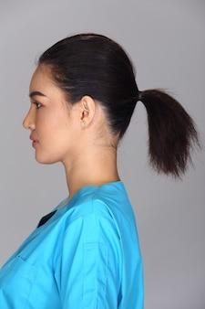 Азиатская женщина после нанесения составляет черную прическу синюю рубашку. без ретуши, свежее лицо с прыщами, красивая и гладкая кожа. студийное освещение серый фон, вид сзади сбоку сзади