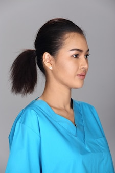 Азиатская женщина после нанесения составляет черную прическу синюю рубашку. без ретуши, свежее лицо с прыщами, красивая и гладкая кожа. студия освещения серый фон