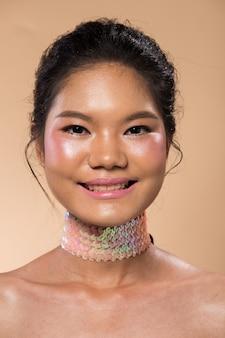 Азиатская женщина после нанесения составляет черную прическу. без ретуши, свежее лицо с угрями, губы, глаза, щека, кожа гладкая. студийное освещение бежевый желтый фон, эстетическая терапия