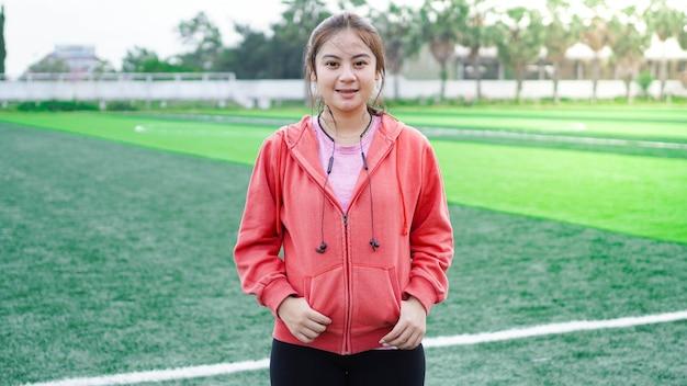 착용 재킷과 이어폰을 실행 한 후 아시아 여자
