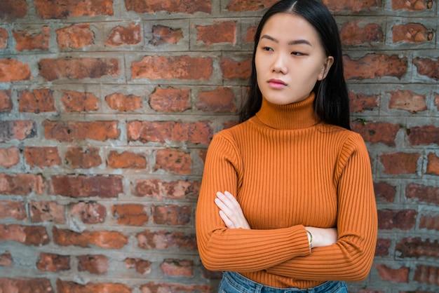 Азиатская женщина против кирпичной стены.