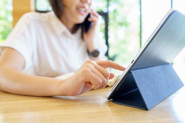 Азиатская женщина в возрасте 30-35 лет, пользующаяся цифровым планшетом с технологией устройства наслаждения