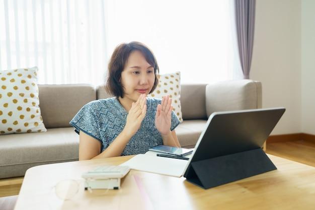 Азиатская женщина в возрасте 30-35 лет с помощью планшета смотрит урок онлайн-курса языка жестов