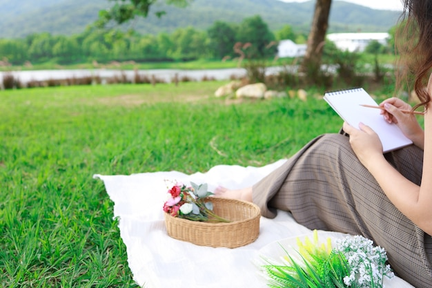 Asian woman alone resting on a picnic in nature park outside at sunny day
