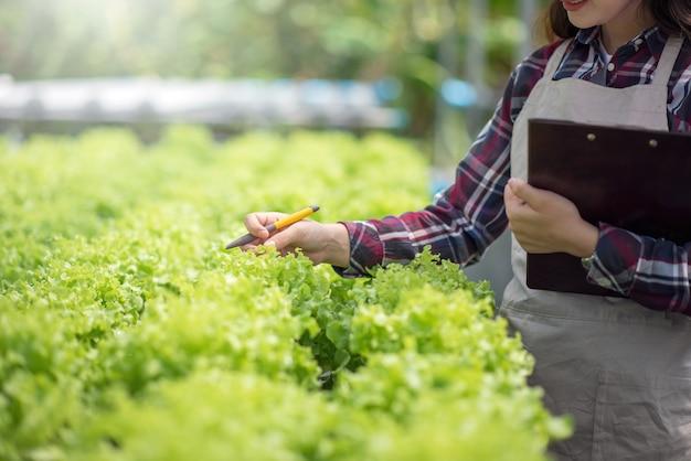 Азиатская женщина анализирует и изучает исследования органических овощных горшков