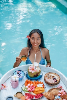 アジアの女性とアジア料理。黒髪の若い女性は、フローティングテーブルとジュースのカップとプールでポーズをとる。