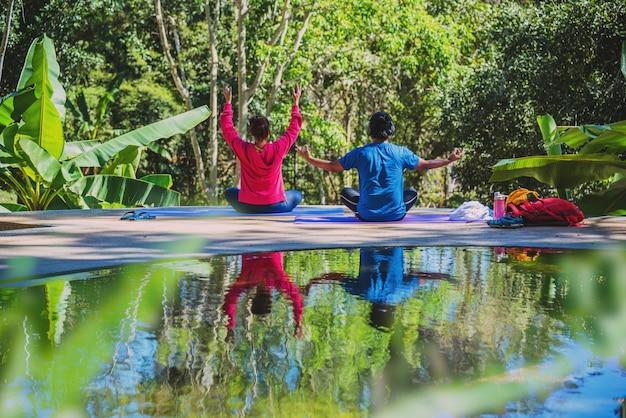 아시아 여자와 아시아 남자는 자연을 여행합니다. 여행 휴식. 요가 자세 개념, 요가 자세로 건강 관리. 야외 운동 릴렉스 요가.