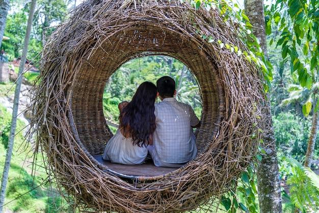 인도네시아 발리 섬의 계단식 논 근처 열대 정글에 있는 새 둥지에 앉아 시간을 즐기고 있는 아시아 여성과 남성. 자연과 여행 개념