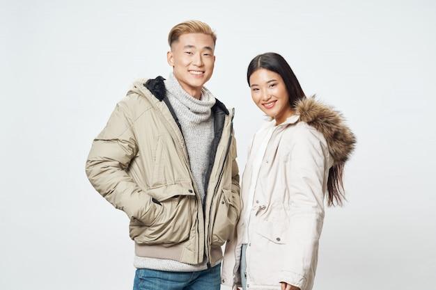 Азиатская женщина и мужчина на ярком цветовом пространстве позирует модели вместе