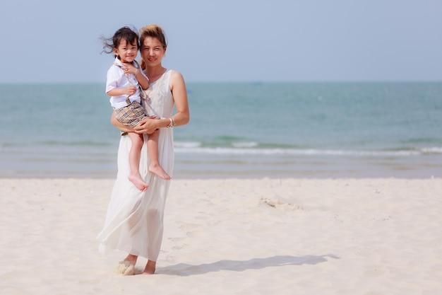 Азиатская женщина и сын на тропическом пляже