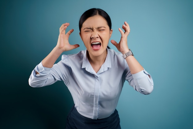 Asian woman angry and shouting isolated on blue.