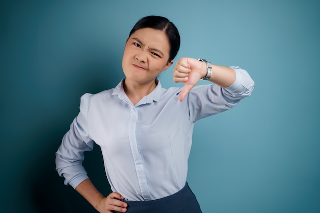 Asian woman annoyed and showing thumb down isolated on blue.