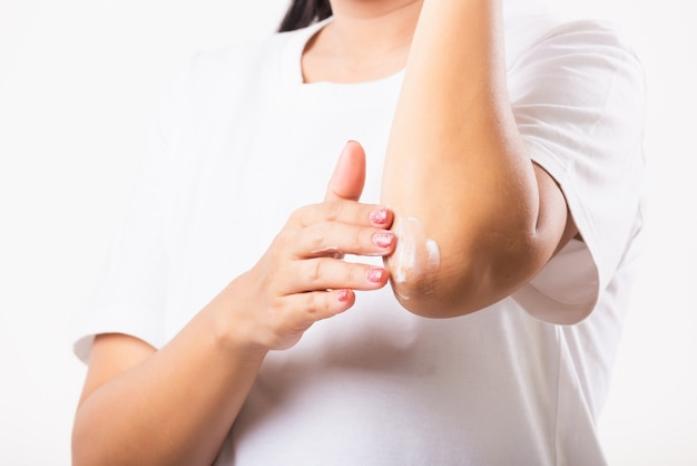 アジアの女性は彼女の肘にローションクリームを適用します