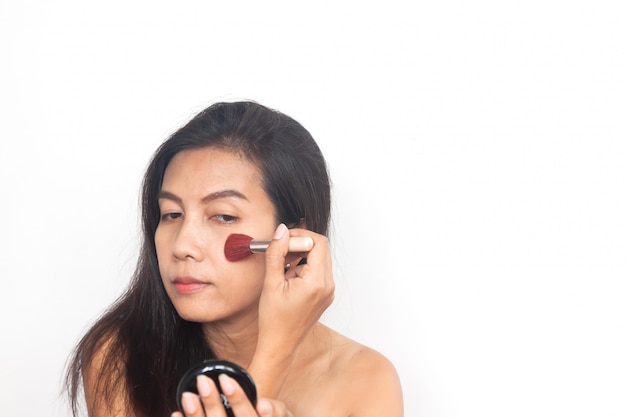 Asian woman applying brush on cheeks. make up and beauty . anti aging and surgery.