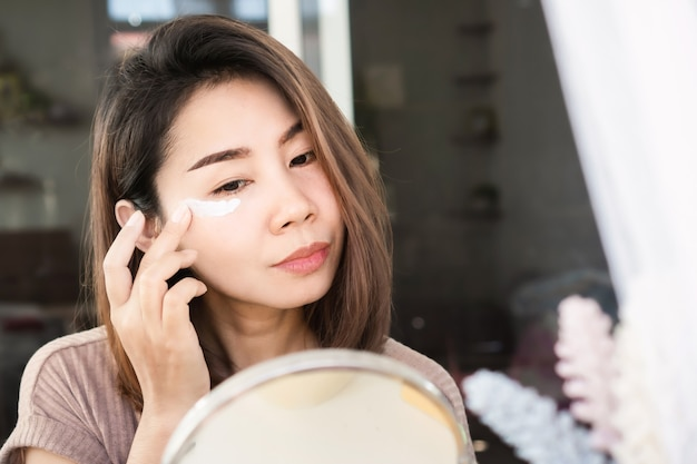 Asian woman applying eye cream, anti aging moisturizing under eyes