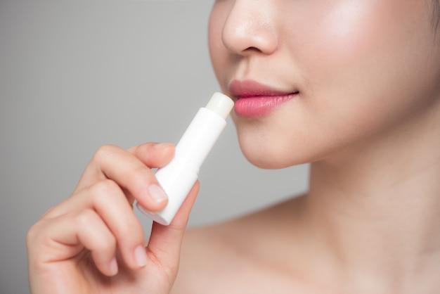 灰色の背景の上に衛生的なリップクリームを適用するアジアの女性