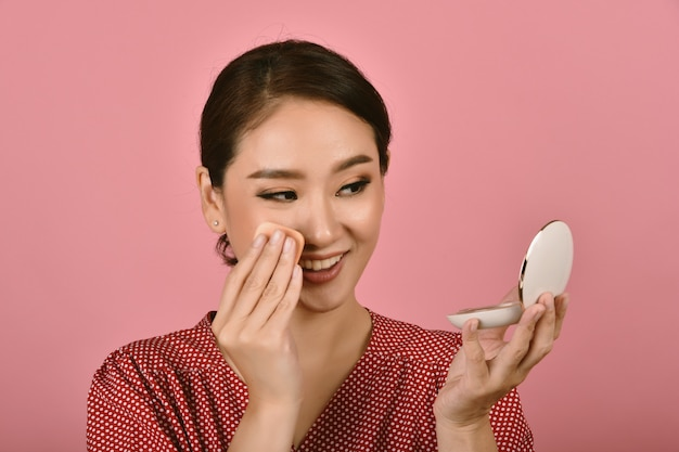 Asian woman applying makeup cosmetics.