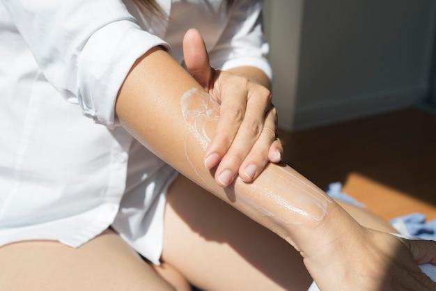 그녀의 팔에 썬 스크린을 적용하는 아시아 여자