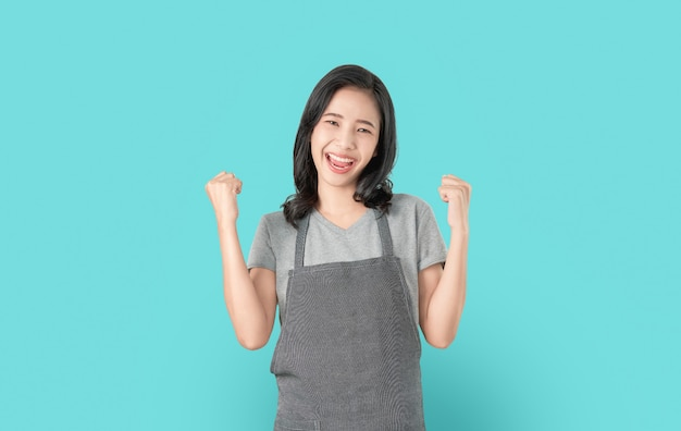 Asian woman in apron and standing with amazed for success and looking forward on blue.