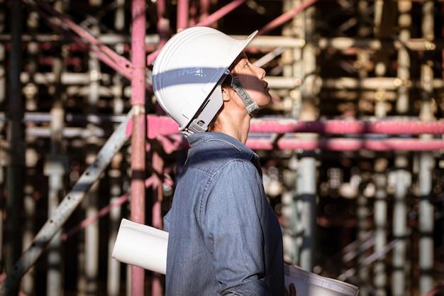 아시아 여성 건축가 또는 건설 엔지니어 흰색 하드 헬멧을 입고 백그라운드에서 비 계와 건설 현장 내부 청사진을 잡아.