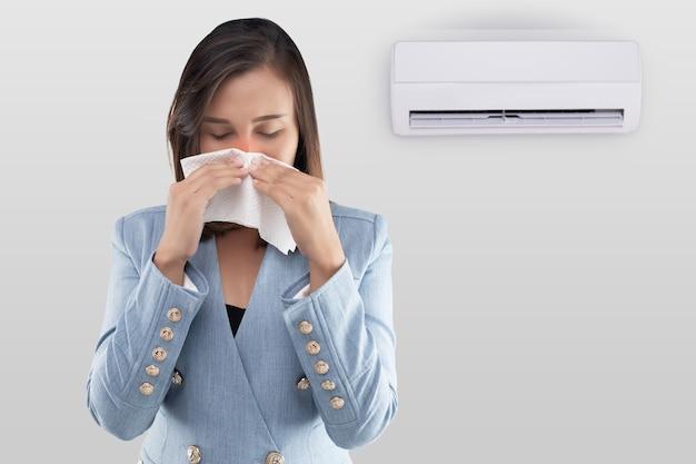 Азиатка закрывает нос из-за затхлого запаха кондиционера