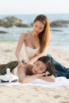 Asian woman are happy and relaxed massage at a spa on the beach in the evening.