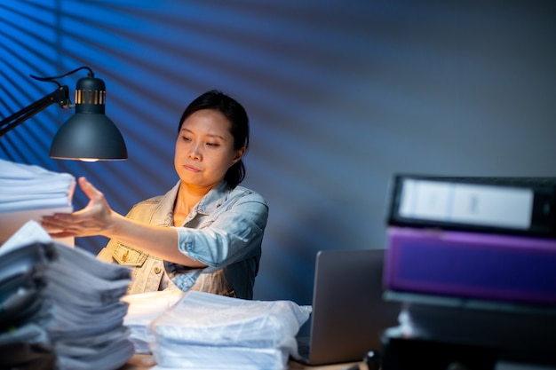 アジアの女性は、オフィスで夜に彼女のマネージャーに官僚レポートフォルダを準備するためのドキュメントを手配します。ドキュメントは職場でデータを整理します。中国の女の子はテーブルに紙の財務を積み重ねます。