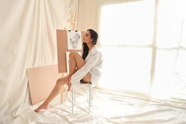 Азиатская женщина-художник в белой рубашке делает перерыв во время рисования рисунка карандашом (концепция образа жизни женщины)