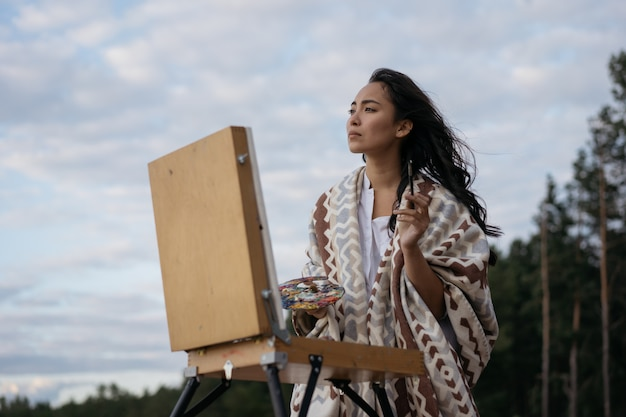 Asian woman artist painting picture on canvas outdoor. authentic portrait of cheerful korean painter holding paintbrush and colorful palette, admire beautiful landscapes and amazing sunset in park