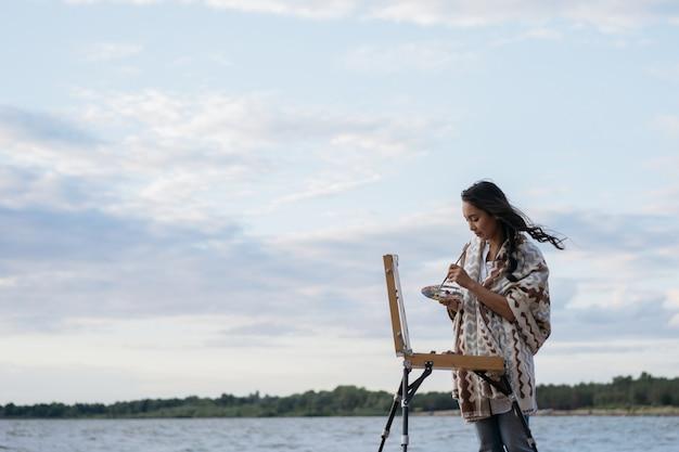 アジアの女性アーティストがキャンバスに絵を描いて、素晴らしい夕日を楽しむ