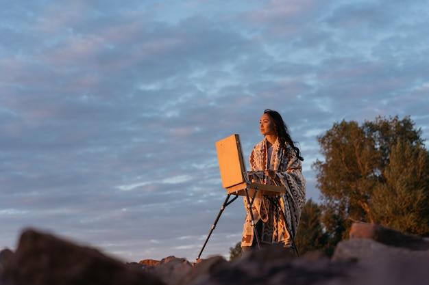 アジアの女性アーティストがキャンバスに絵を描いて、インスピレーションを探し、素晴らしい夕日を楽しむ