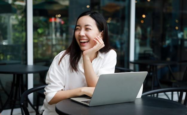 ラップトップに取り組んでいるカフェでアジアの女性