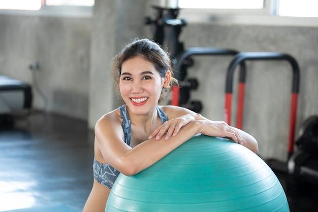 웃 고 행복 한 그녀의 공에 기대어 포즈 요가 체육관에서 아시아 여자.