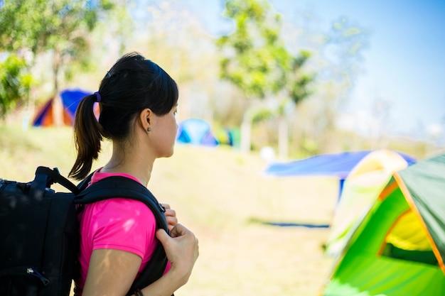 Азиатская женщина рюкзак, чтобы пойти в походную палатку для занятий в летнем лагере.