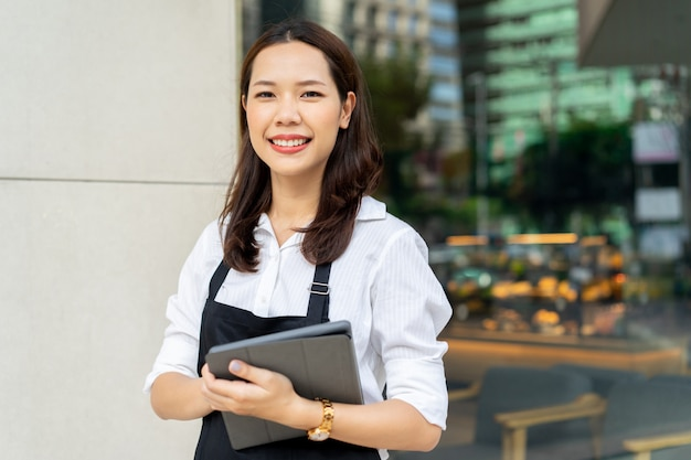 Asian woman barista holding tablet for checking order from customer on blurred coffee cafe shop