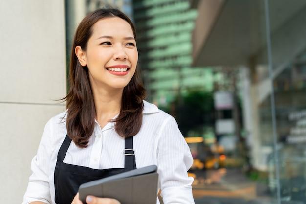 Азиатская женщина бариста держит планшет для проверки заказа от клиента