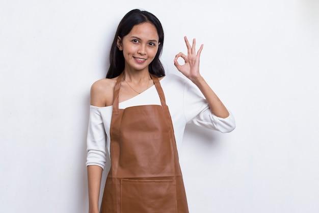 아시아 여성 바리스타 웨이트리스가 앞치마를 입고 확인 표시 제스처가 흰색 배경에 격리되어 있습니다.