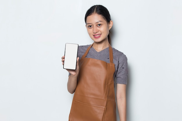 Asian woman barista wear apron demonstrating mobile cell phone cafe service concept