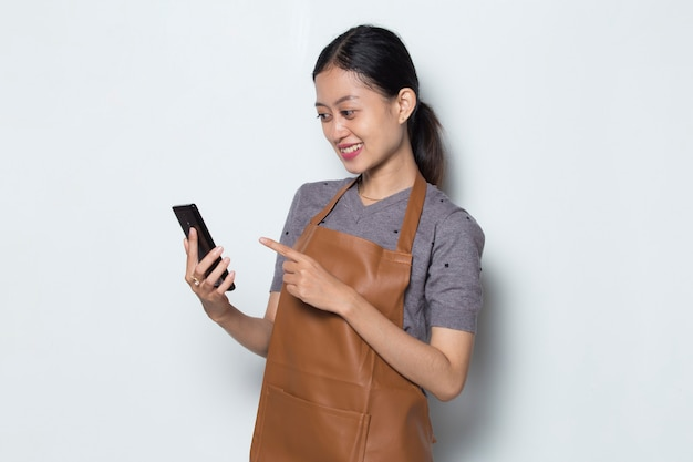 Asian woman barista wear apron with mobile phone cafe service concept
