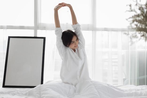 아시아 여자 아름다운 젊은 웃는 여자가 침대에 앉아 침실 af에서 아침에 스트레칭